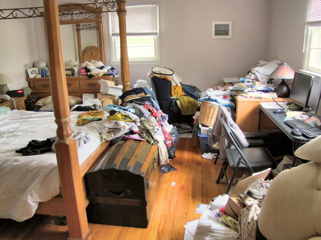 a bedroom completely covered by clothes and laundry