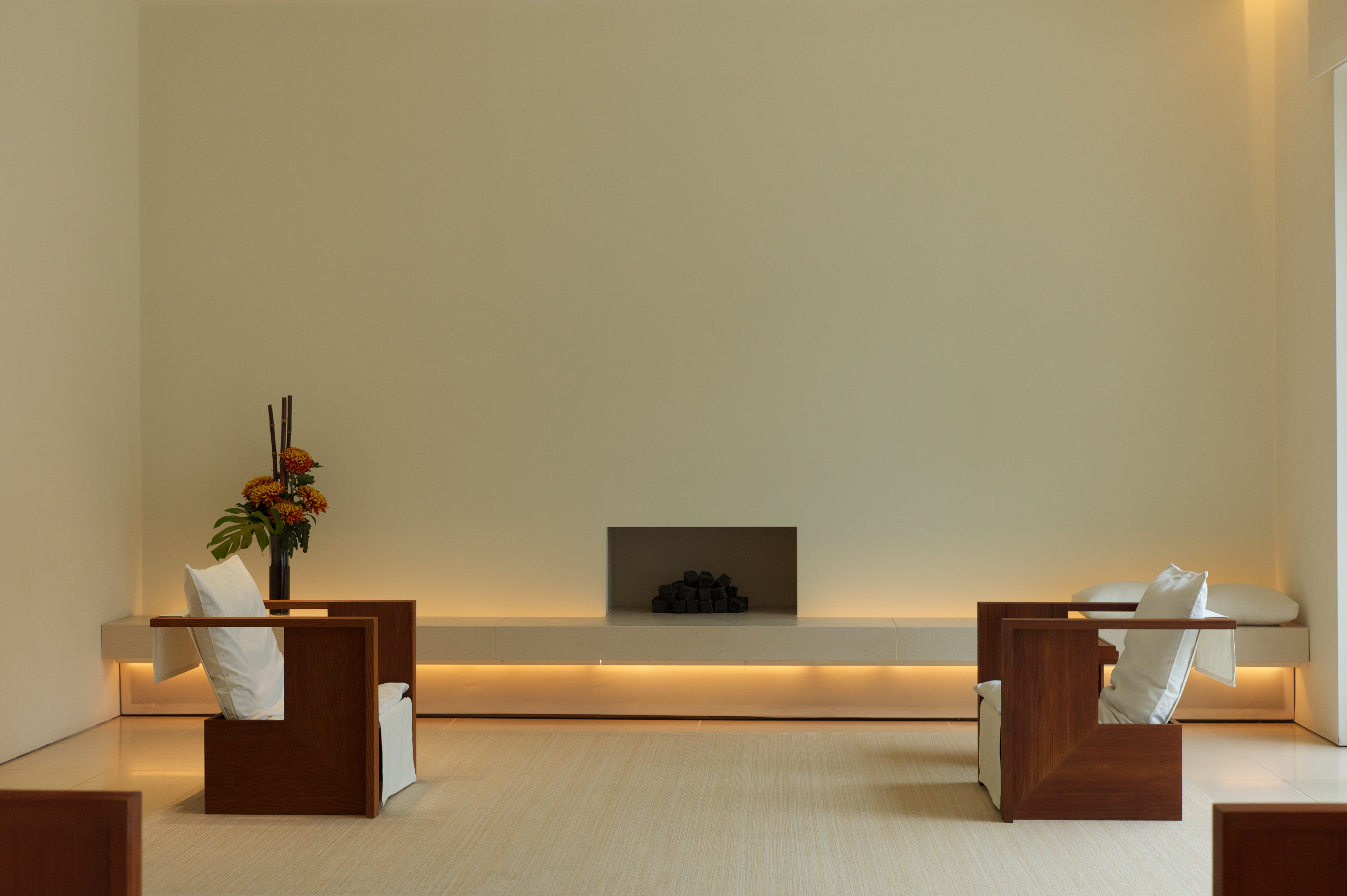 A very simple room with two chairs spaced far apart and a small fireplace between them,