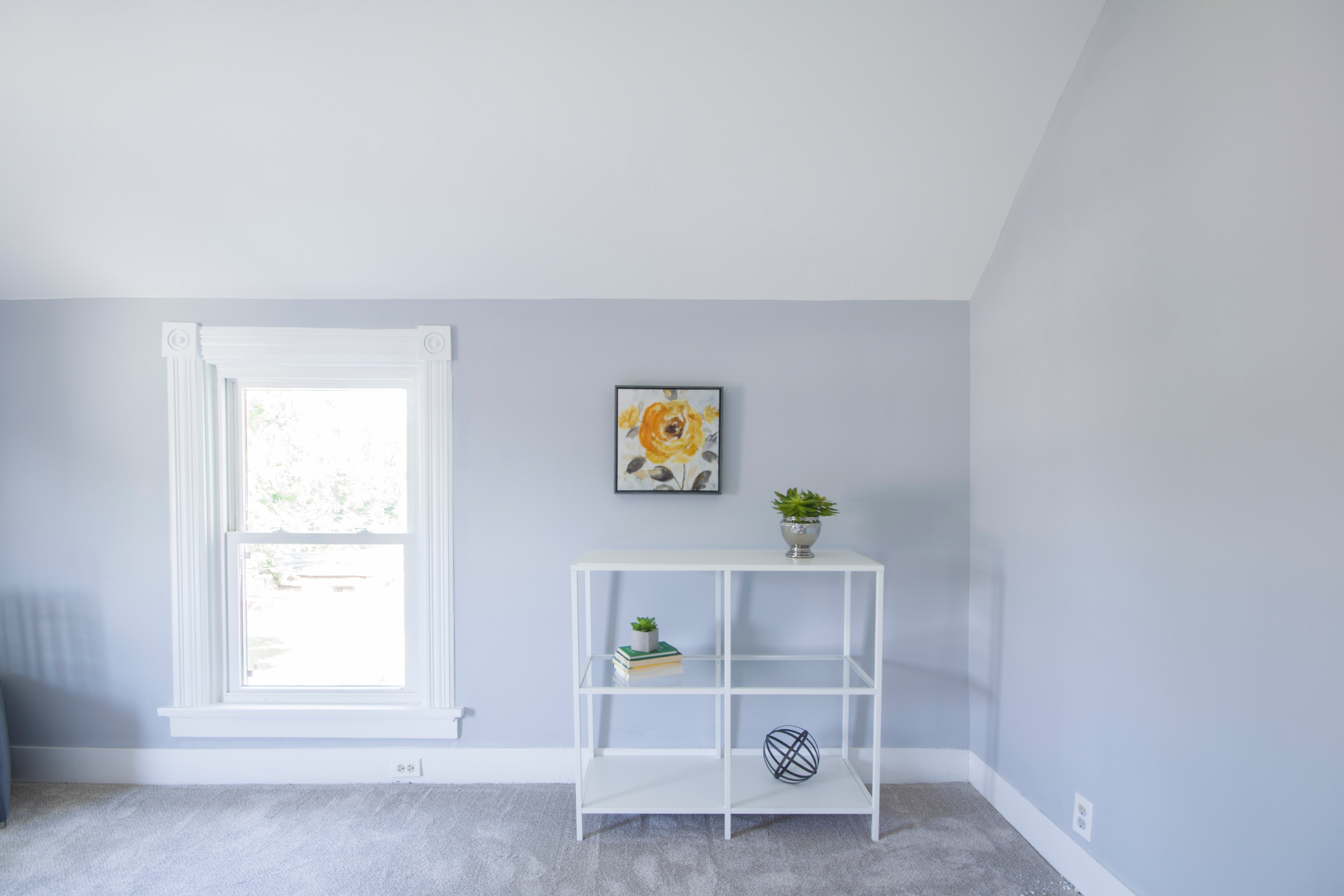 a minimalist white room with a simple shelf holding 3 succulents, a painting of a sunflower sits behind