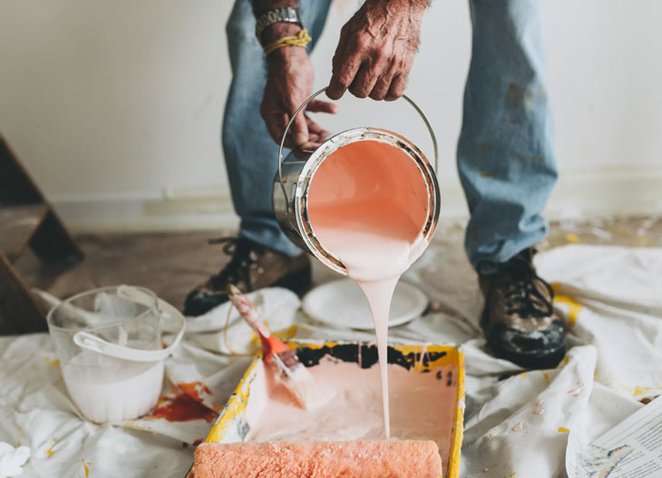 person holding pink paint bucket pouring