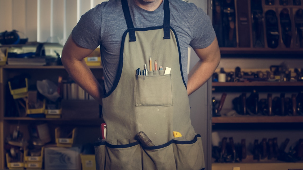 Guy wearing apron full of tools