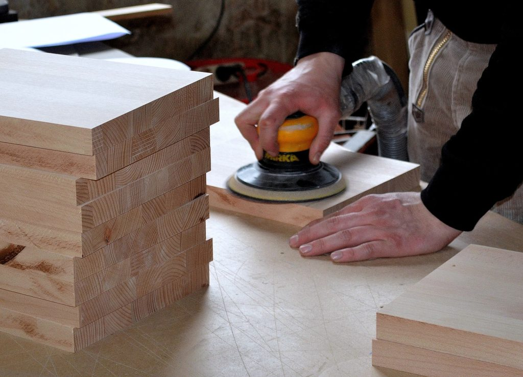 A carpenter working on pieces of wood on  workbench